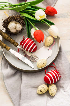Table setting for Easter dinner with tulips and eggs on white wooden table Standard-Bild