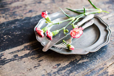Festive table setting for spring dinner with fresh flowers on dark wooden table