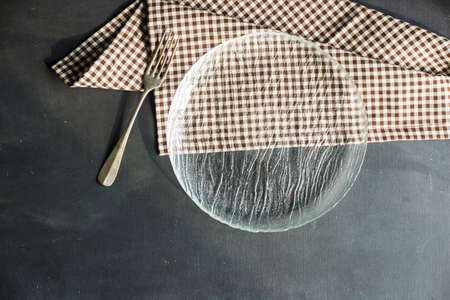 Rustic table setting with empty plate and vintage fork on dark wooden table