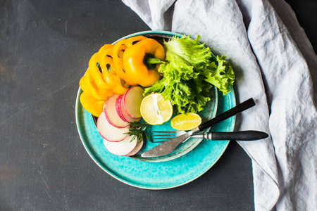 Healthy food concept yellow  sliced bell pepper, radish vegetables and letuce leaves on a rustic plate