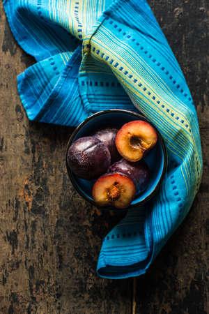 Healthy food concept fresh orgaic plums in a rustic bowl