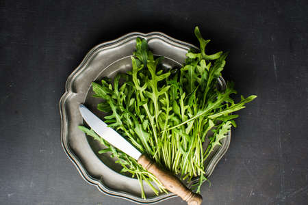 Organic food concept with fresh leaves of ruccola herb on dark background