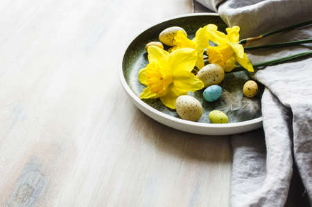 Festive table setting for Easter dinner with bright easter eggs and yellow daffodils Stock Photo