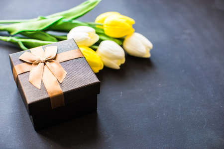 git: Tulips and git box on dark background Stock Photo