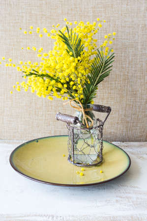 Festive table setting for Easter dinner with bright easter eggs and mimosa flowers on rustic plate