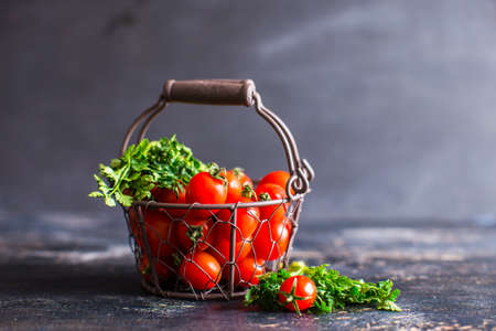 Vintage meta busket full of fresh organic cherry tomatoes and parsley herb on dark wooden table