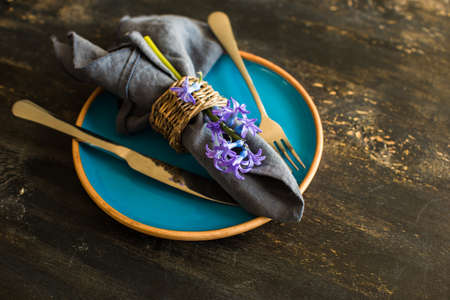 napkin ring: Bouquet of bright blue hyacinth flowers on rustic plate in festive spring table setting Stock Photo