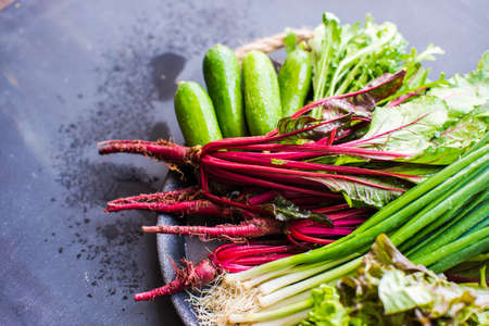 Organic vegetables like a beets, green onion, rukkola, lettuce on dark wooden background