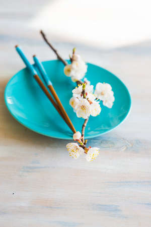 Spring table setting with chopsticks and peach blooming on a wooden table