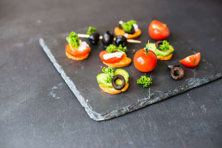 Bruschetta with cheese and vegetables on dark wooden table