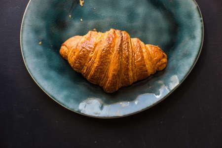 Fresh homemade french croissant on dark wooden table