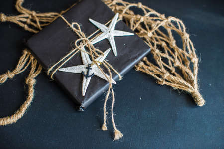 Summer gift concept with gift and sea shells and sea stars on rustic dark background