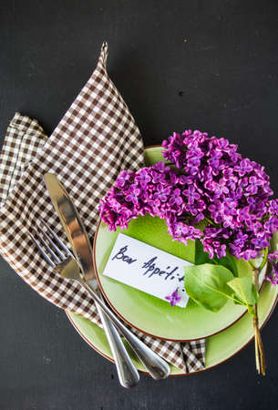 Spring table setting with bright lilac flowers on rustic background with copyspace