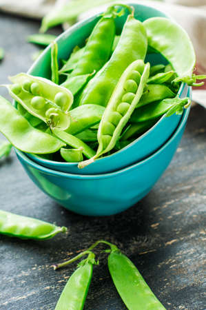 pea pod: Organic green peas on rustic background Stock Photo
