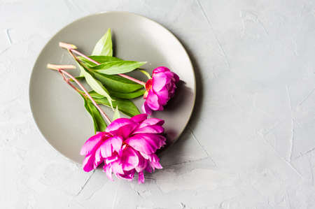 Summer festive table setting with beautiful purple peonies and vintage flatware on grey concrete background with copyspace