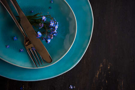 Summer floral table setting with bright blue forget-me-not flowers on wooden table Stock Photo