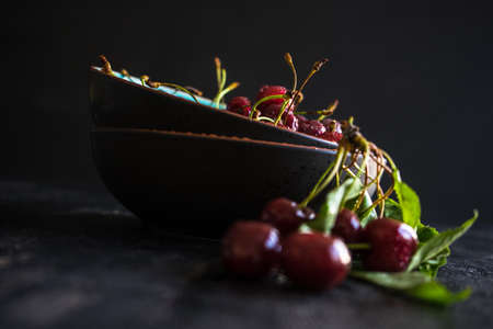 Organic food concept ripe red sweet cherries on dark wooden table Stock Photo