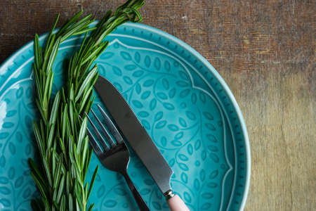 Summer table setting with bright blue plate and fresh rosemary on vintage wooden table