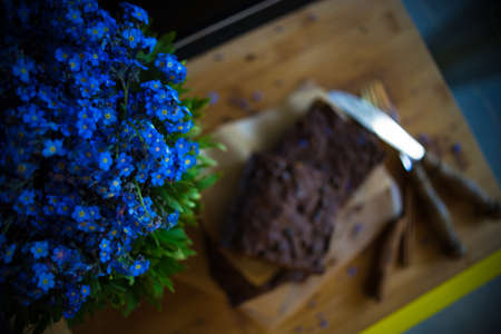 Chocolate cake brownie and forget-me-not flowers on dark rustic table Stock Photo