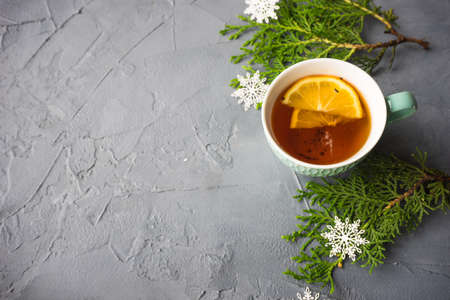 Cup of tea with lemon on rustic concrete background with Christmas decoration