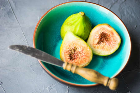 Organic fig tree fruits on the vintage plate on concrete background with copyspace