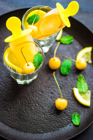 Summer dessert with lemon and mint on rustic wooden background with copyspace