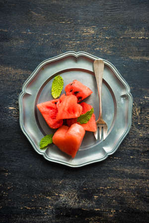 Organic sweet watermelon heart shaped pieces on vntage plate decorated with mint on rustic wooden table Stock Photo