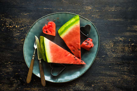 Organic sweet watermelon heart shaped pieces on vntage plate decorated with mint on rustic wooden table with copyspace