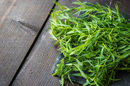 Tarragon herb as a organic salad ingredient on dark wooden table Imagens