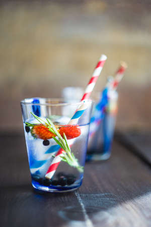 Detox summer drink with rosemary, strawberry, and bilberry with bright color straws on dark wooden table