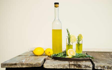 伝統的なイタリアのレモン アルコール飲み物リモンチェッロ レモンとローズマリーのハーブ暗い木製のテーブルの上の部分と
