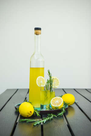 Traditional italian lemon alcohol drink limoncello with pieces of lemon and rosemary herb on dark wooden table