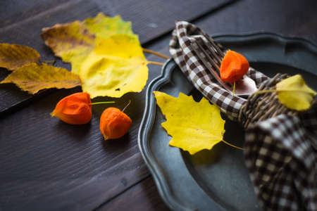 Autumnal table setting with bright yellow leaves and physalis  on old wooden table with copyspace Stock Photo