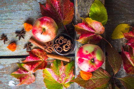 Autumnal cooking concept with ripe apples and spices for pie like a cinnamon sticks and anose star on wooden table with bright yellow and red leaves Stock Photo