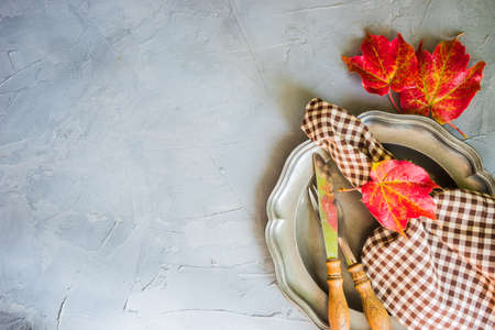Festive autumnal table setting with bright red and yellow leaves with copyspace
