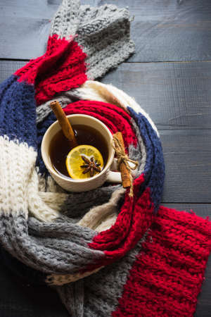 pinecones: Cup of tea with lemon and winter spices like a cinnamon sticks and anise star with warm  knitted scarf on dark wooden table with copyspace Stock Photo