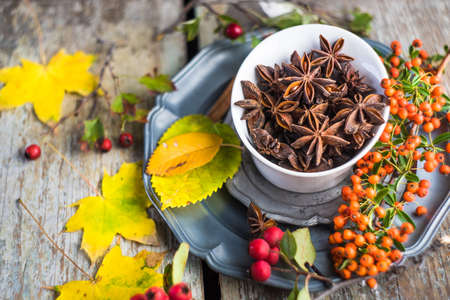 Bowl full of anise star on wooden vintage background with bright yellow autumnal leaves and berries Stock Photo