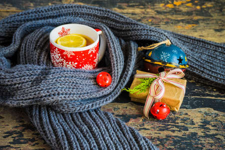Red cup of tea with lemon, Christmas lights and decoration on rustic background with copyspace Stock Photo