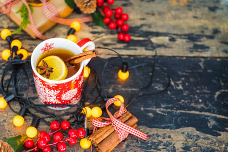 encendedores: Red cup of tea with lemon, Christmas lights and decoration on rustic background with copyspace Foto de archivo