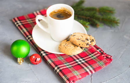 Cup of coffee with chocolate cookies and Christmas decoration on grey concrete background with copy space