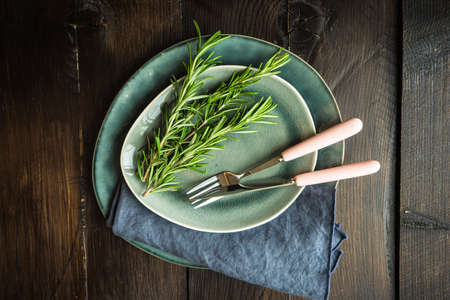 Rustic table setting with vintage tableware  and rosemary herb  on  a table with copyspace Stock Photo