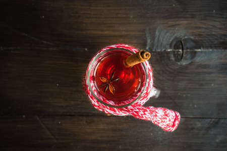 Mulled wine in a glass on rustic wooden table