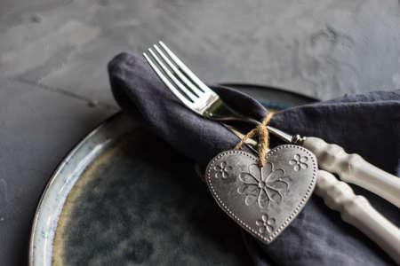 コンクリートグレーの背景にヴィンテージハート型の装飾とバレンタインデーのお祝いのディナーのための素朴なテーブルの設定