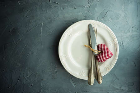 Rustic table setting for festive  dinner in Valentines Day with vintage heart-shaped decor on concrete grey background