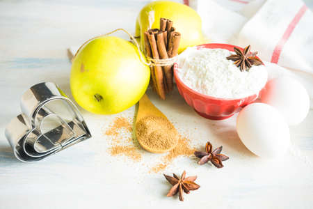 Christmas baking concept with apples, cinnamon sticks, sugar, anise star and flour on white wooden table