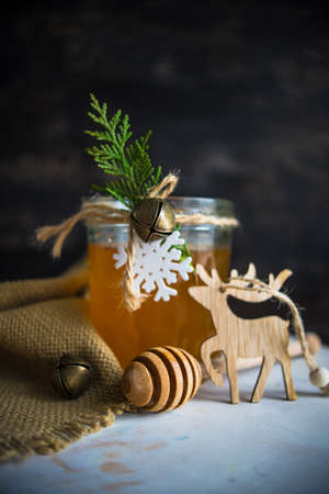 Christmas holiday concept with organic honey decorated with fir tree and jinglebells on rustic background Stock Photo