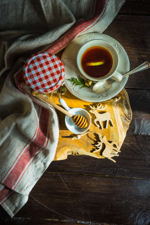 Organic honey and cup of tea for breakfast as a sweet dessert concept