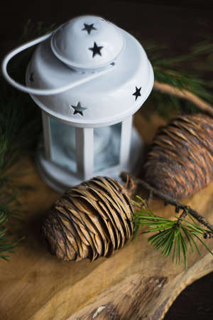 Christmas holiday concept with fir tree, cones and white lamp on rustic background with copyspace