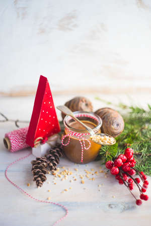 Organic nut butter with holiday winter decorations and nuts on white vintage table with copyspace