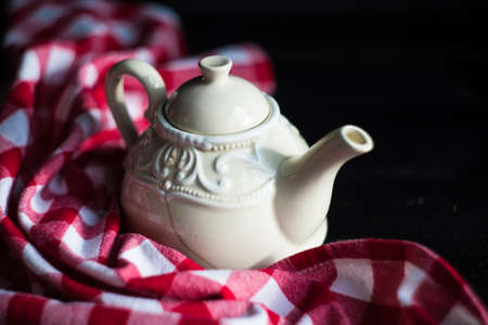 Vintage tea pot and red rustic napkin on wooden table Stock Photo